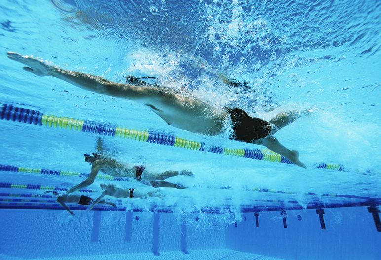 Male swimmers racing in pool, underwater view
